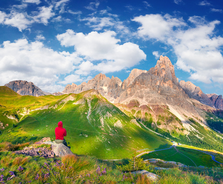 Climber admiring of view of the Pale di San Martino summit. Colorful summer morning in the Dolomite Alps, San Martino di Castrozza village location, Italy. Beauty of nature concept background.