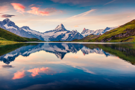 Colorful summer sunrise on Bachalpsee lake with Schreckhorn and Wetterhorn peaks on background. Picturesque morning scene in the Swiss Bernese Alps, Switzerland, Europe.  Foto de archivo