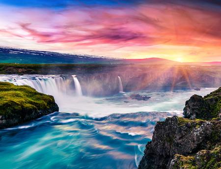 Cena inacreditável da manhã do verão na cachoeira de Godafoss. Nascer do sol colorido no no rio de Skjalfandafljot, Islândia, Europa. Beleza do fundo do conceito de natureza.