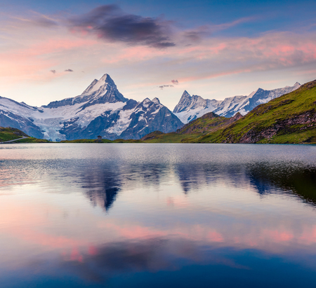 Schreckhorn mountain reflected in Bachalpsee lake. Colorful summer sunrise in the Swiss Bernese Alps, Switzerland, Europe. Beauty of nature concept background.