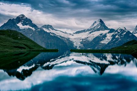 Dramamtic summer evening on Bachalpsee lake with Schreckhorn and Wetterhorn peaks on background. Dark outdoor scene in the Swiss Bernese Alps, Switzerland, Europe.