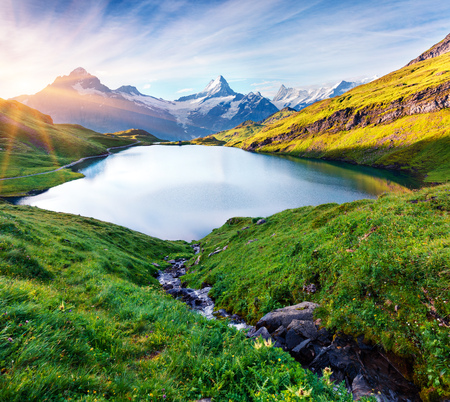 Colorful summer sunrise on Bachalpsee lake with Schreckhorn and Wetterhorn peacks on background. Green morning scene in the Swiss Bernese Alps, Switzerland, Europe.
