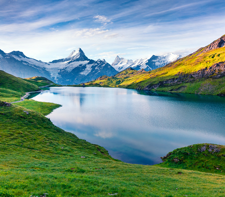 Dramatic summer view of the Bachalpsee lake with Schreckhorn peak on the background. Colorful morning scene in the Swiss Bernese Alps, Switzerland, Europe. Beauty of nature concept background.
