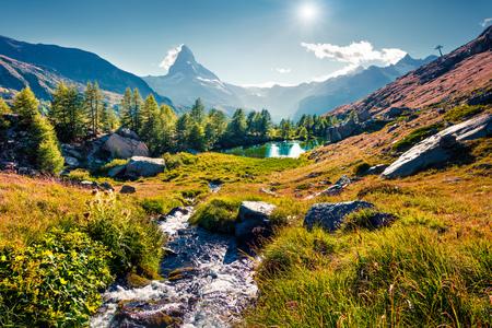 Colorful summer sunrise on the Grindjisee lake. Reflection of Matterhorn (Monte Cervino, Mont Cervin) peak in the watter surface. Beautiful outdoor scene in Swiss Alps, Zermatt location, Switzerland. Stock Photo