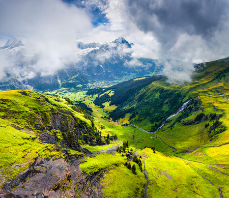 Unbelievable summer view from the top of Grindelwald First cableway. Schreckhorn mountain in the morning mist, Grindelwald village location, Swiss Bernese Alps, Switzerland, Europe.