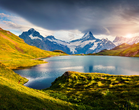 Colorful summer evening on Bachalpsee lake with Schreckhorn and Wetterhorn peaks on background. Green morning scene in the Swiss Bernese Alps, Switzerland, Europe. Beauty of nature concept background.