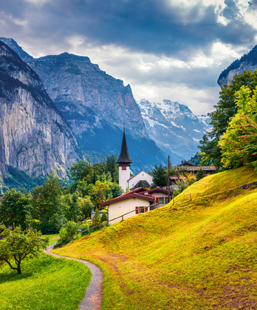 Sunny summer view of Lauterbrunnen village with old town hall. Splendid outdoor scene in Swiss Alps, Bernese Oberland in the canton of Bern, Switzerland, Europe. Beauty of countryside concept background.