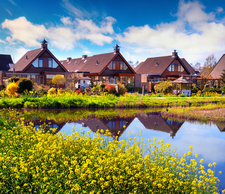 Sunny spting morning in with typical Holland building on the water canal. Beautiful outdoor scene in the Netherlands, Zaanstad village village location, Europe. Beauty of countryside concept background.