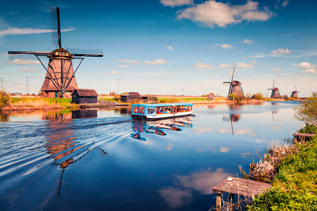 Famous windmills in Kinderdijk museum in Holland. Sunny spring morning in countryside. Colorful outdoor scene in Netherlands, Europe. Artistic style post processed photo.