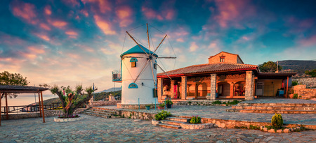 Picturesque morning scene of the countryside with windmill. Colorful spring sunrise on the Zakynthos island, Korithi location, Ionian Sea, Greece, Europe.