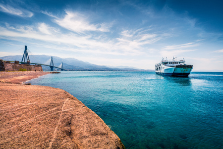 Sunny morning scene of Rion-Antirion Bridge and ferryboat. Colorful spring view of the Gulf of Corinth, Greece, Europe.