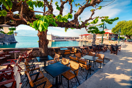 Sunny spring scene of the outdoor cafe in Nafpaktos town. Fantastic morning scene of the Gulf of Corinth, Greece, Europe.