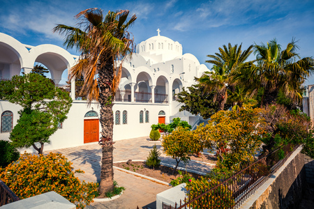 Sunny spring view of garden at Fira Orthodox Cathedral. Colorful morning scene of the famous Greek resort - Thira, Santorini, Greece, Europe. Stock Photo