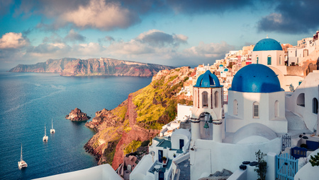 Sunny morning view of Santorini island. Picturesque spring sunrise on the famous Greek resort Oia, Greece, Europe.