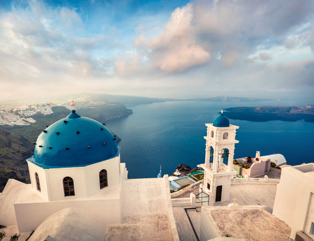 Misty morning view of Santorini island. Picturesque spring scene of the famous Greek resort Fira, Greece, Europe. Stock Photo
