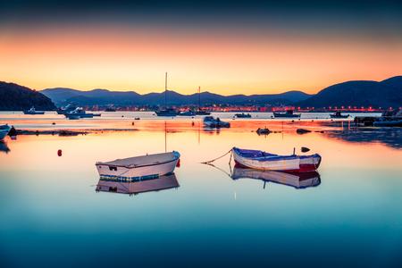 Splendida scena primaverile della spiaggia Nuevo Loca, sul Mar Egeo. Vista drammatica di sera della città di Anavyssos, Grecia, Europa.