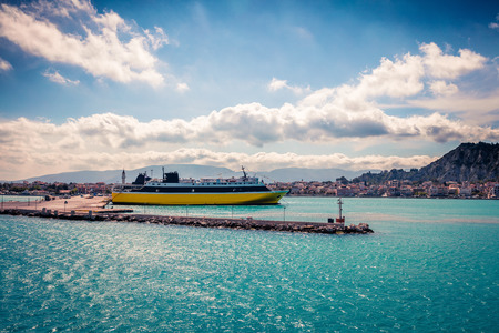 Sunny morning scene of Zakynthos city and ferryboat. Colorful spring view of the Ionian Sea, Greece, Europe.