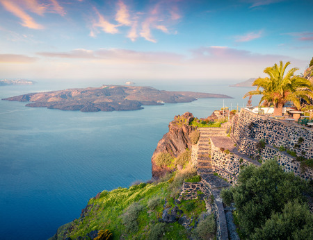 Sunny morning view of Santorini island. Picturesque spring sunrise on the famous Greek resort Thira, Greece, Europe. Traveling concept background. Artistic style post processed photo. Stock Photo