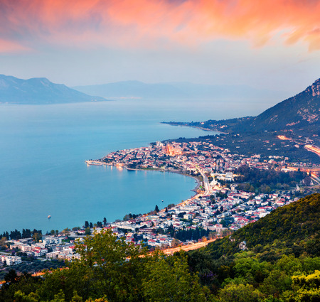 View from the birds-eye of Kamena Vourla town in the evening mist. Colorful spring cityscape in Greece, Europe. Beautiful sunset on Aegean Sea. Artistic style post processed photo.