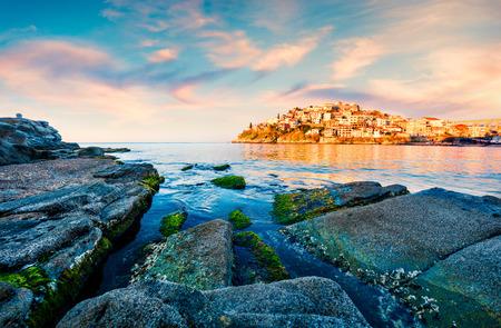 Beautiful spring view of Aegean Sea. Coloful sunrise in Kavala city, the principal seaport of eastern Macedonia and the capital of Kavala regional unit. Greece, Europe.