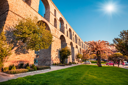 Cityscape with medieval aqueduct Kamares in the Kavala city. Sunny spring evening in the Macedonia, Greece, Europe. Traveling concept background. Artistic style post processed photo.