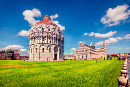 Picturesque spring view of famous Leaning Tower in Pisa. Sunny morning scene with hundreds of tourists in Piazza dei Miracoli (Square of Miracles), Italy, Europe. Traveling concept background.