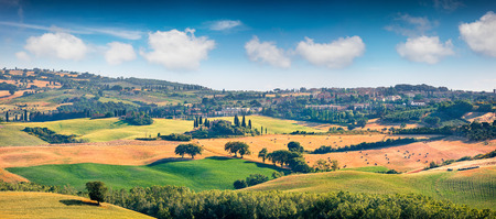 Wheat harvest in Tuscany. Typical Tuscan view of San Quirico dOrcia. Colorful summer view of Italian countryside. Beauty of countryside concept background.