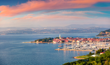 Aerial view of old fishing town Izola. Impressive spring sunset in Slovenia, Europe. Beautiful seascape Adriatic Sea. Traveling concept background.