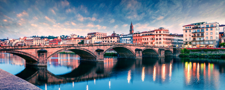 Picturesque medieval arched Ponte alla Carraia bridge over Arno river. Colorful spring sunset in Florence, Italy, Europe. Traveling concept background. Фото со стока