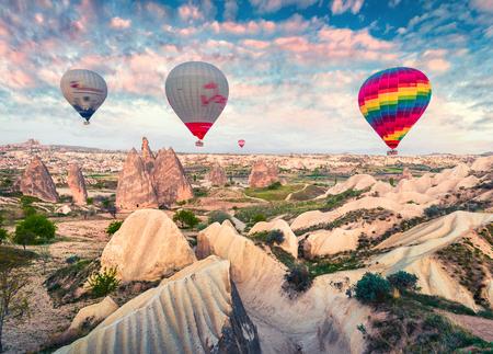 Fliegen auf den Ballons am frühen Morgen in Kappadokien. Bunte Frühlingssonnenaufgang im Red Rose Valley, Göreme Dorflage, Türkei, Asien. Reisen Konzept Hintergrund.