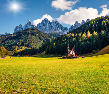 Picturesque view of Chiesetta di San Giovanni in Ranui church in front of the Geisler or Odle Dolomites Group. Colorful autumn sunset in Dolomite Alps, Italy, Europe. Traveling concept background.