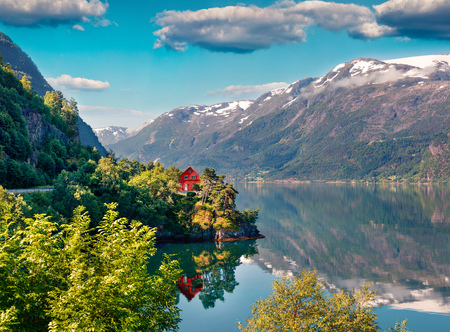 Impressive summer view of red painted house on the shore of Hardangerfjord fjord, Hordaland county, Norway. Beauty of countryside concept background.