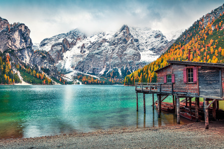 Boat hut on Braies Lake with Seekofel mount on background. Colorful autumn landscape in Italian Alps, Naturpark Fanes-Sennes-Prags, Dolomite, Italy, Europe. Traveling concept background.