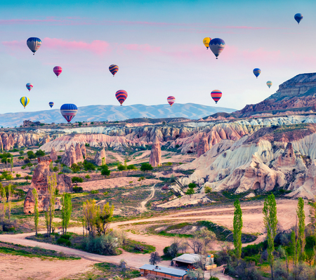 Flying on the balloons early morning in Cappadocia. Colorful spring sunrise in Red Rose valley, Goreme village location, Turkey, Asia. Traveling concept background.