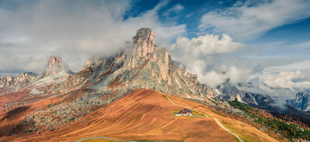 Foggy morning panorama from the top of Giau pass with famous Ra Gusela, Nuvolau peaks in background. Colorful autumn scene of Dolomite Alps, Cortina dAmpezzo location, Italy, Europe. Stock Photo