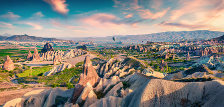 Unreal world of Cappadocia. Colorful sunrise in Red Rose valley in April. Cavusin village located, district of Avanos in Nevsehir Province in the Cappadocia region of Turkey, Asia. Traveling concept b 写真素材