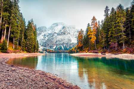 First snow on Braies Lake. Colorful autumn landscape in Italian Alps, Naturpark Fanes-Sennes-Prags, Dolomite, Italy, Europe. Beauty of nature concept background. Stock Photo