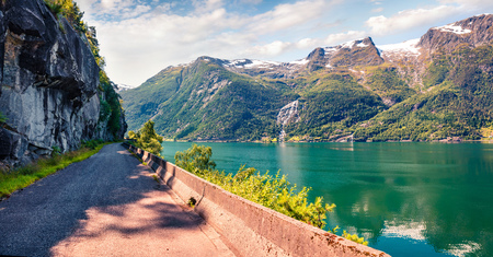 Sunny summer scene ofLofthus village in Ullensvang municipality which is located in the Hardanger region of Hordaland county, Norway. Colorful morning view of Hardangerfjord fjord. Traveling concept background. Stock Photo