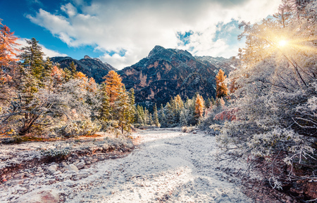 First snow in Naturpark Fanes-Sennes-Prags. Colorful autumn landscape in Dolomite Alps, Braies Lake location,  Italy, Europe. Artistic style post processed photo. Stock Photo