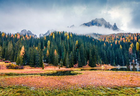 Foggy outdoor scene of Misurina lake. Colorful autumn morning in Dolomite Alps, National Park Tre Cime di Lavaredo, Italy, Europe. Beauty of nature concept background. Stock Photo - 116546521