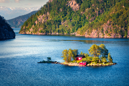 Picturesque summer view with small island with typical Norwegian building on Lovrafjorden flord, North sea. Colorful morning view in Norway. Beauty of nature concept background.