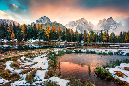 Dramatic sunrise on Antorno lake. Picturesque autumn morning in Dolomite Alps, Province of Belluno, Italy, Europe. Beauty of nature concept background. Stock Photo