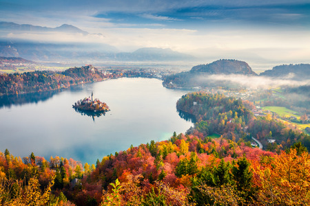 Aerial view of church of Assumption of Maria on the Bled lake. Foggy autumn landscape in Julian Alps, Slovenia, Europe. Beauty of countryside concept background. Stok Fotoğraf - 116546565