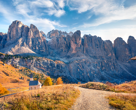 Small church on the top of Gardena pass with Piz Boe mountain on background. Colorful autumn scene in the Dolomite Alps, Canazei, Province of Trento, Italy, Europe. Beauty of countryside concept background.