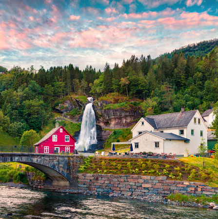 Splendid summer sunset with Large, popular waterfall Steinsdalsfossen on the Fosselva River. Picturesque evenig scene of  village of Steine village, municipality of Kvam in Hordaland county, Norway. Stock Photo