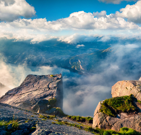Misty morning view of popular Norwegian attraction Preikestolen. Great summer scene of the Lysefjorden fjord, located in the Ryfylke area in southwestern Norway. Beauty of nature concept background.
