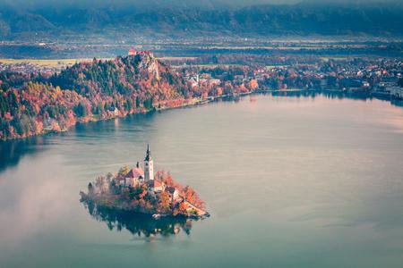 Vista aérea de la iglesia de la Asunción de María en el lago Bled. Paisaje de otoño brumoso en Alpes Julianos, Eslovenia, Europa. Belleza del fondo del concepto de campo. Foto de archivo