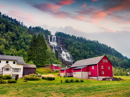 Colorful summer sunrise with Tvindefossen waterfall. Picturesque morning scene with typical Norwegian buildings, Hordaland county, Norway. Beauty of countryside concept background. Stock Photo