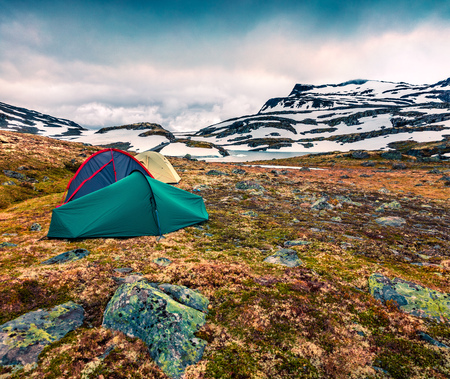 Three tourist tents on a mountain plateau in Norway. Picturesque summer view of tne North countryside. Active tourism concept background. Banco de Imagens