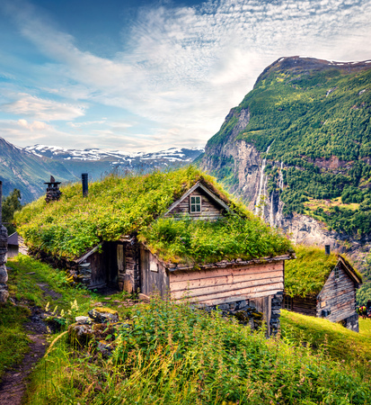 Norwegian typical grass roof wooden old house on the Seven Sister waterfall on background. Colorful summer morning in Norway, Europe. Beauty of countryside concept background. 스톡 콘텐츠 - 116546962